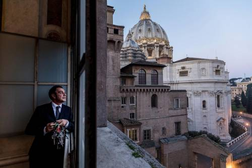 """Italy: Ông Giovanni Crea đang nhìn ra cửa sổ của Bảo tàng Vatican vào lúc sáng sớm, trong ca làm buổi sáng lúc 5h30 của mình. """"Mỗi sáng, khi bước vào Nhà nguyện Sistine, tôi luôn trải qua rất nhiều cảm xúc. Khi làm công việc này, tôi là người nắm giữ chìa khóa của toàn bộ lịch sử đạo Thiên Chúa"""", ông nói. Bảo tàng Vatican là nơi cất giữ những bộ sưu tập hiện vật lịch sử, hội họa đồ sộ của Thiên Chúa giáo."""